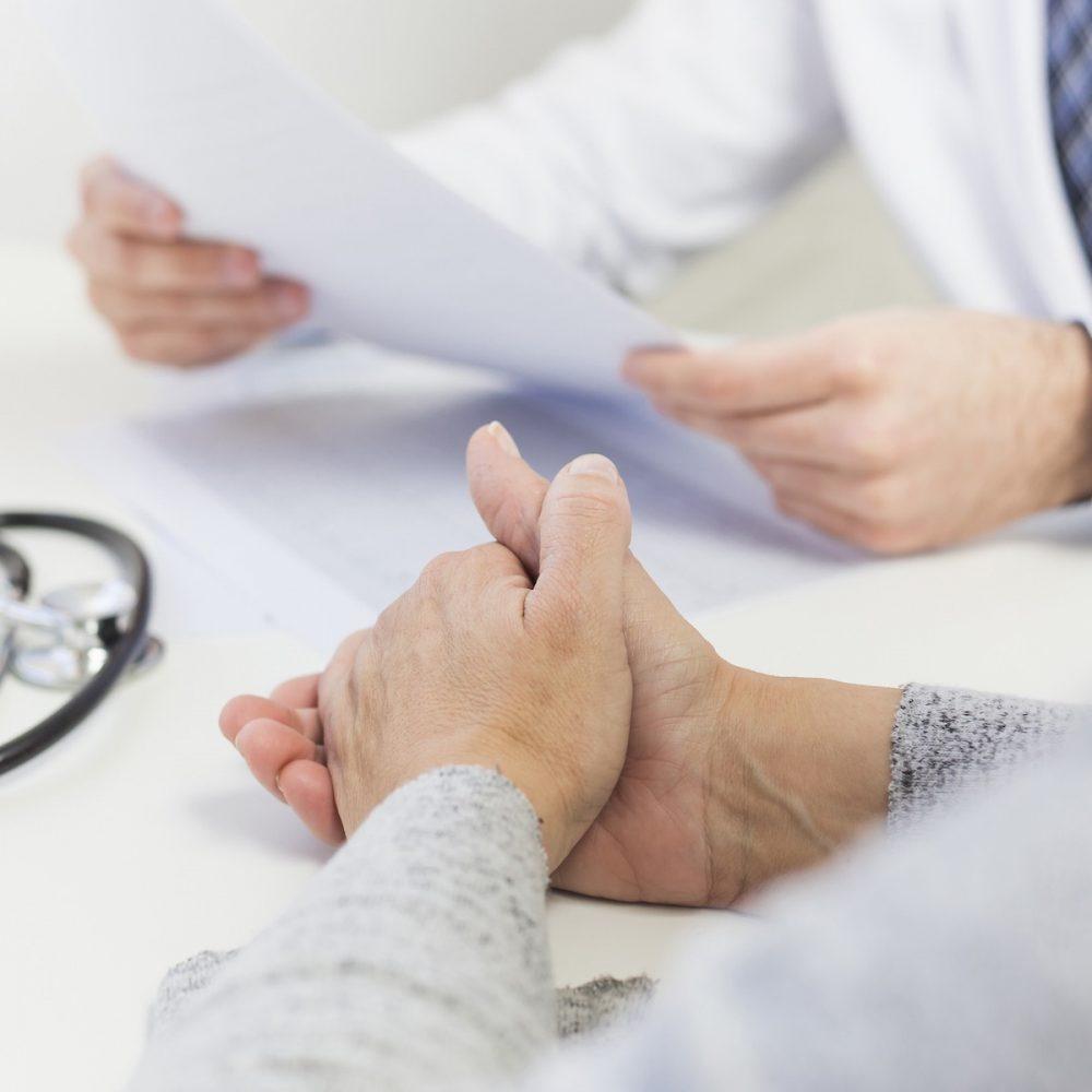 vrouwelijke-geduldige-patient-dichtbij-de-arts-medisch-rapport-houdt-573857-PLOMP3-827